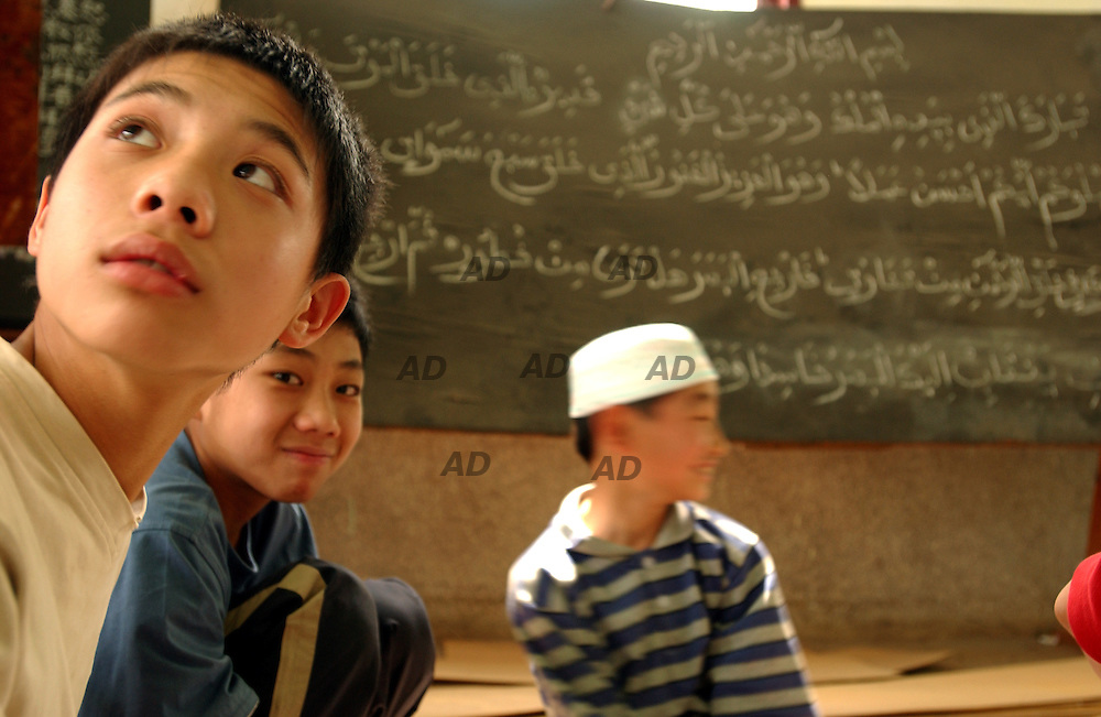 Young muslims in the Shadian mosque. On the blackboards the arab words written during the arab lessons.