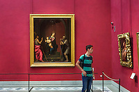 "FLORENCE, ITALY - 29 JUNE 2016: A vistor looks at a painting in the ""Michelangelo and the Florentines"" in the Uffizi Gallery in Florence, Italy, on June 29th 2016.<br /> <br /> Art historian Eike Schmidt, former curator and head of the Department of Sculpture, Applied Art and Textiles at the Minneapolis Institute of Arts, became the first non-Italian director of the Uffizi in August 2015, replacing Antonio Natali who directed the gallery for 9 years. One of the main goals of the new director is to open the Vasari Corridor to the general public. Currently the corridor can only be visited with group reservations made by external tour and travel agencies throughout the year.<br /> <br /> The Vasari Corridor is is a 1-kilometer-long (more than half mile) elevated enclosed passageway which connects the Palazzo Vecchio with the Palazzo Pitti, passing through the Uffizi Gallery and crossing the Ponte Vecchio above the Arno River, in Florence. The passageway was designed and built in 1564 by Giorgio Vasari in only 6 months to allow Cosimo de' Medici and other Florentine elite to walk safely through the city, from the seat of power in Palazzo Vecchio to their private residence, Palazzo Pitti. The passageway contains over 1000 paintings, dating from the 17th and 18th centuries, including the largest and very important collection of self-portraits by some of the most famous masters of painting from the 16th to the 20th century, including Filippo Lippi, Rembrandt, Velazquez, Delacroix and Ensor."