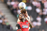 Milton Keynes Dons defender Callum Brittain (25) heads the ball under pressure from Grimsby Town striker JJ Hooper (9) during the EFL Sky Bet League 2 match between Milton Keynes Dons and Grimsby Town FC at stadium:mk, Milton Keynes, England on 21 August 2018.