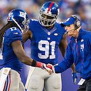 Oct 25, 2015; East Rutherford, NJ, USA; New York Giants head coach Tom Coughlin congratulates New York Giants wide receiver Dwayne Harris (17) after a catch in the 2nd quarter with New York Giants defensive end Robert Ayers (91) onlooking at MetLife Stadium. Mandatory Credit: William Hauser-USA TODAY Sports