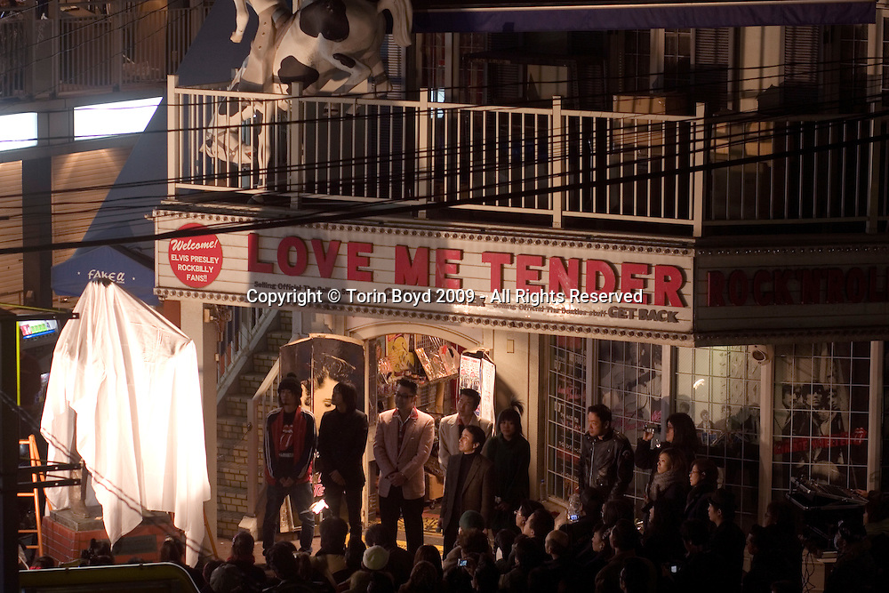"Sayonara to Elvis in Tokyo - white sheet placed over his statue: For the past 24 years, the specialty memorabilia shop called Love Me Tender has been a Tokyo institution dedicated to Elvis Presley. Located in Tokyo's trendy youth hangout of Harajuku, this shop has been a mecca for Japanese Elvis fans as well as a popular attraction for foreign tourists. But on Sunday January 18, 2009 it all came to an end when Love Me Tender closed it doors for good. To mark the occasion a final Sunday concert was held which more resembled a wake. These Sunday rockabilly concerts had been taking place here for the past ten years. According to staff who worked here, Love Me Tender closed for a number of reasons citing the bad economy as well as the land being an attractive prize for real estate speculators. In addition to this shop, also housed here was a Rolling Stones shop called Gimme Shelter and a Beatles shop called Get Back. Collectively the building was called The Rock 'N' Roll Museum. In addition to these shops, just in front was larger than life sized bronze statue of Elvis which had been there since 1992. Sadly ""Elvis Left the Building"" the following day (1/19/09) and only a handful of people were on hand to witness the King being hauled away. For now, the Elvis statue will be kept in storage while the shop's owners can find a permanent home for him. Their ideal location would be in front of Harajuku Station which is sort of a landmark for rock and roll in Japan. After WW II the American military built a large housing project there for military families and during the 1950s and 1960s American teenage subculture flourished here."