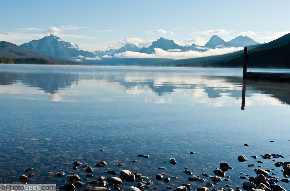 """Lake McDonald reflects peaks of the Livingston Range in Glacier National Park, Montana, USA. Since 1932, Canada and USA have shared Waterton-Glacier International Peace Park, which UNESCO declared a World Heritage Site (1995) containing two Biosphere Reserves (1976). Rocks in the park are primarily sedimentary layers deposited in shallow seas over 1.6 billion to 800 million years ago. During the tectonic formation of the Rocky Mountains 170 million years ago, the Lewis Overthrust displaced these old rocks over newer Cretaceous age rocks. Glaciers carved spectacular U-shaped valleys and pyramidal peaks as recently as the Last Glacial Maximum (the last """"Ice Age"""" 25,000 to 13,000 years ago). Of the 150 glaciers existing in the mid 1800s, only 25 active glaciers remain in the park as of 2010, and all may disappear by 2020, say climate scientists."""