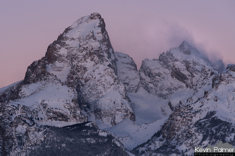 Grand Teton awaits the first light of day under a soft pink sky while clouds swirl around Mount Owen.