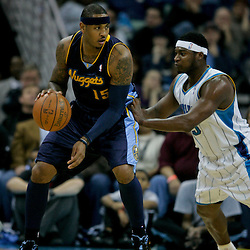 Dec 18, 2009; New Orleans, LA, USA; Denver Nuggets forward Carmelo Anthony (15) is guarded by New Orleans Hornets guard Devin Brown (23) during the first half at the New Orleans Arena. Mandatory Credit: Derick E. Hingle-US PRESSWIRE