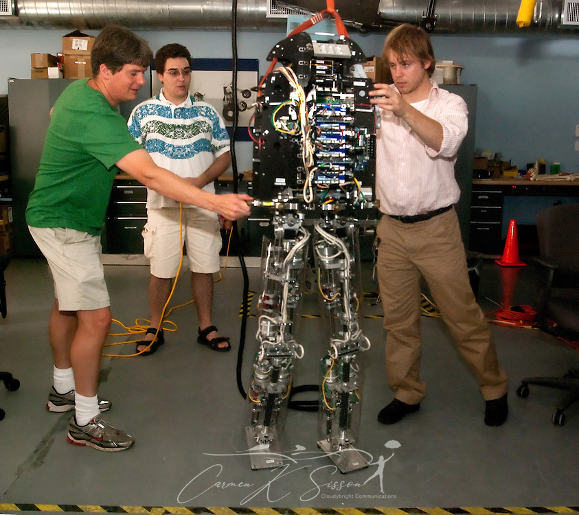 Research scientist Jerry Pratt and associates Phil Demonaco and Riewart van Doesburgh take turns shoving M2V2, a bipedal robot, to gauge its recovery time Nov. 13, 2009 at the Institute for Human and Machine Cognition in Pensacola, Fla. M2V2 is unique in its ability to mimic human heel-to-toe motion and right itself without falling when slightly pushed. Pratt says it's not yet mastered being pushed backwards though and will still sometimes fall. (Photo by Carmen K. Sisson/Cloudybright)