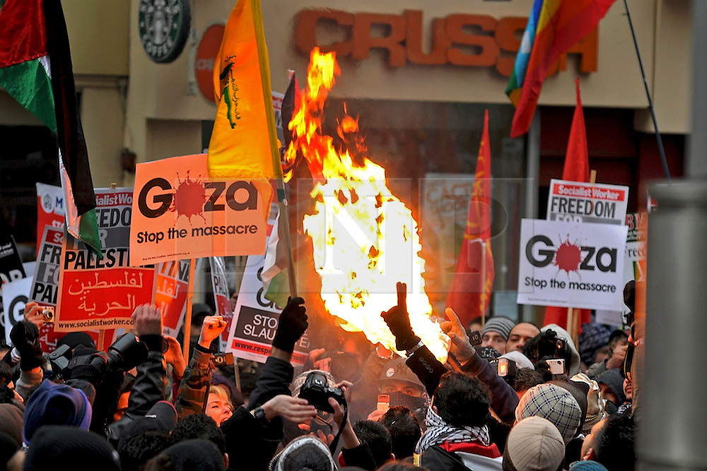10/01/09 A banner is set alight during clashes outside the Israeli Embassy in protest against the war in Gaza
