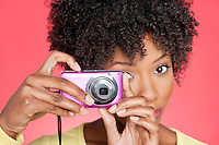 Portrait of an African American woman taking picture from camera over colored background
