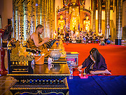 07 APRIL 2013 - CHIANG MAI, CHIANG MAI, THAILAND:  A Buddhist Monk blesses a woman at Wat Chedi Luang in Chiang Mai, Thailand. Wat Chedi Luang is the most important temple in Chiang Mai and was the main temple of the Lanna Kingdom, before it was absorbed by Thailand, then Siam, in the late 18th century. Chiang Mai is the largest town in northern Thailand and is popular with tourists and backpackers.       PHOTO BY JACK KURTZ