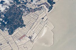 An astronaut aboard the International Space Station focused near the Sun's reflection point to shoot this photograph of grid-patterned fish farms on the coast of China's northeast province of Liaoning. The aquaculture basins have been built out from the wooded coast to a distance of nearly 6 kilometers (4 miles). Fish farms have been constructed at many points along the provincial coastline, but this group of basins facing the Yellow Sea is the largest. (Liaoning Province is the sixth in China in terms of aquaculture production.)<br /> The basins are built on shallow seabeds, mudflats, and bays.<br /> Islands, such as the one at image center, often help anchor the construction of basins. Outer barriers protect the basins from winter storms. Water flow lines and a ship wake are visible near the river estuary.<br /> Most aquaculture products are marketed live in China, with less than 5 percent processed for local or overseas markets.<br /> Shellfish, a traditional marine food source, still dominates the marine species production (77 percent), with sea fish a distant second (5 percent).<br /> About 4.3 million people are involved in freshwater and marine fish production in China (as of 2007).<br /> Click here to view another high-contrast astronaut photograph of fish farms near the Nile Delta.<br /> Astronaut photograph ISS044-E-89407 was acquired on September 6, 2015, with a Nikon D4 digital camera using an 1150 millimeter lens, and is provided by the ISS Crew Earth Observations Facility and the Earth Science and Remote Sensing Unit, Johnson Space Center. The image was taken by a member of the Expedition 44 crew. The image has been cropped and enhanced to improve contrast, and lens artifacts have been removed. The International Space Station Program supports the laboratory as part of the ISS National Lab to help astronauts take pictures of Earth that will be of the greatest value to scientists and the public, and to make those images freely available on the Internet. Additional images taken by astronauts and