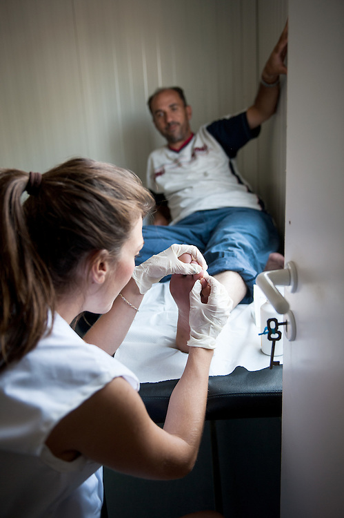 MSF nurse Daphne Garefou gives a treatment to a man with blisters at the medical centre in Kara Tepe camp.