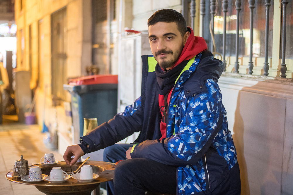 Young adult male sitting on streets and brewing Turkish coffee, Istanbul, Turkey