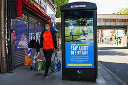 © Licensed to London News Pictures. 12/05/2020. London, UK. Shoppers wearing face coverings walk past a 'STAY ALERT TO STAY SAFE' billboard in north London, which is a part of the government's new public information campaign as the lockdown is gradually eased. Photo credit: Dinendra Haria/LNP