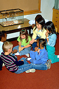 Students playing with hamster in school classroom age 6.  St Paul  Minnesota USA
