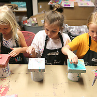 """Lucy Christian, 5, of Tupelo, Katie Coker, 7, of Blue Springs, and Allie Grisham, 7, also of Blue Springs, work on their """"Chalk Paint Pour"""" project at their Art/DIY Camp at Farmhouse in Tupelo on Tuesday morning."""