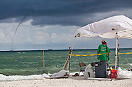 7/16/2010 BP oil spill clean up worker in Gulf Shores Alabama stop for the day as a waterspout hits the Gulf of Mexico.