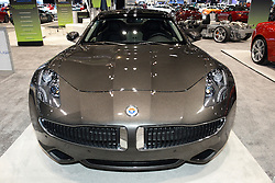 08  February 2013: Exotic Car display - Fiskar Karma EcoSport. Chicago Auto Show, Chicago Automobile Trade Association (CATA), McCormick Place, Chicago Illinois<br /> <br /> 2013 FISKER KARMA ECOSPORT: There are two Fisker Karma EcoSport models in the Comcast Business Class Garage exhibit at the 2013 Chicago Auto Show. This is a great opportunity to get close to the world's first luxury plug-in exotic four-door, four passenger sedans. The Karma powertrain features dual electric rear motors, rear wheel drive with mid-mounted battery pack and front/mid mounted 260 horsepower turbocharged 2.0 liter gasoline engine/generator. The electric drive motors generate a total of 403 hp, and is linked to a single speed fixed gear transmission. An advanced regenerative blended brake system is employed for maximum energy recapture, along with extruded aluminum spaceframe, modular chassis subassembly, aluminum and composite body panels for improved driving range and outstanding performance. All-electric 'Stealth Mode' powers the Fisker Karma with a Lithium-ion battery for up to 50 miles total distance. When in 'Sport Mode', the Lithium-ion battery works in combination with the internal combustion engine for a total range of 250 miles. Fisker can streak from 0-to-60 mph in 5.9 seconds and reach a top speed of 125 mph. Custom Fisker Karma designed 22-inch wheels come framed with Goodyear tires, and the low-slung Fisker height is only 4.4 feet. Luxurious cabin includes animal free material to reflect pure leather grain, and the wood used is rescued pieces retrieved from the 2007 firestorm in Orange County, CA, and certified sunken wood from the bottom of Lake Michigan. The Fisker's examples at the show are courtesy of Patrick Dealer Group, and have sticker prices of $116.600.