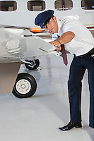 Portrait of happy young male pilot inspecting airplane's wing