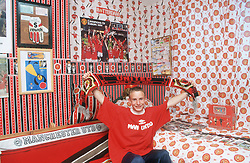 Young male Manchester United football fan sitting in bedroom covered with posters waving supporter's scarf,