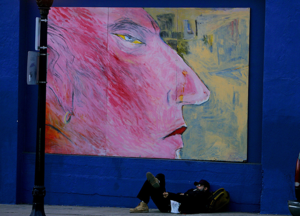 A homeless man smokes a cigarette in Downtown San Diego with a mural above him.