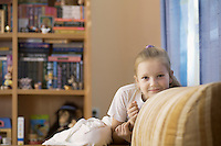 Girl smiles at camera in playroom with shelving storage