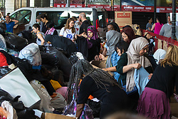 London, June 15th 2017. Mountains of food and clothing donated to the many people who have lost everything and been made homeless in the Grenfell Tower fire of June 14th, by generous Londoners are categorised and stored on a basketball court at the Westway Sports Centre and other locations near to the scene of the fire. PICTURED: Volunteers struggle to keep up with the sheer volume of donations streaming in to various centres.