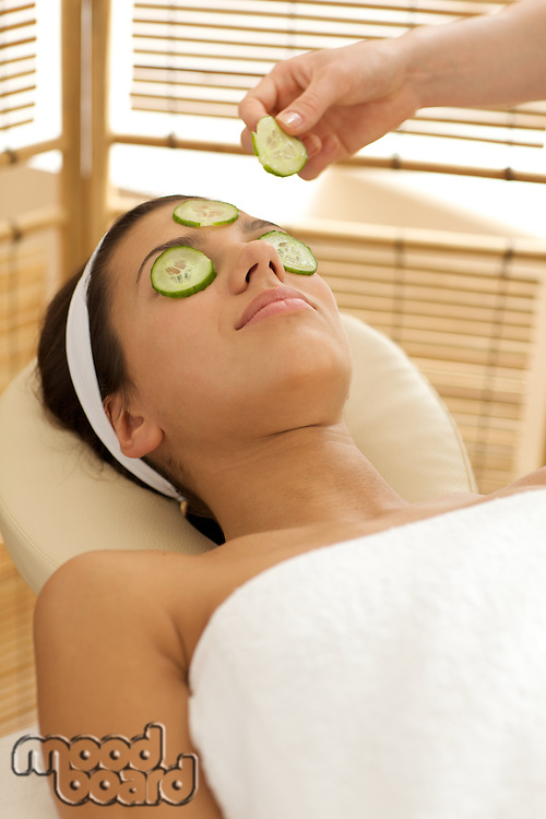 Young woman lying on massage table with cucumber slice being placed over eye