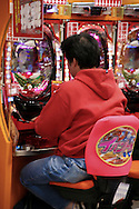 Pachinko is a Japanese gaming device used for amusement and even prizes. Although pachinko machines were originally strictly mechanical, modern pachinko machines are a cross between a pinball machine and a video slot machine. The machines are widespread in establishments called pachinko parlors, which also often feature a number of slot machines. Pachinko parlors almost always are done up in  garish decoration,  a haze of cigarette smoke; the constant din of the machines, music and announcements and flashing lights.