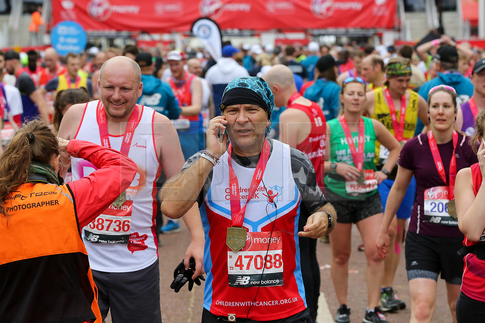 © Licensed to London News Pictures. 28/04/2019. London, UK. A runners on the mobile phone after completing the 2019 Virgin Money London Marathon. Photo credit: Dinendra Haria/LNP