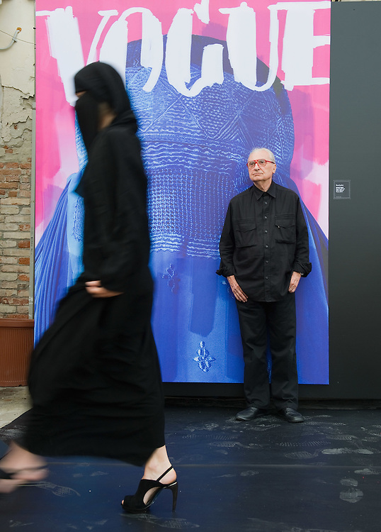 "VENICE, ITALY - JUNE 01:  Creator of fashion magazines and artist Flavio Lucchini poses with a model in front of his work ""poster/vogue"" part of the exhibition ""What Women Want (?)"" on June 1, 2011 in Venice, Italy. The exhibition addresses the controversiat theme of the burqa"