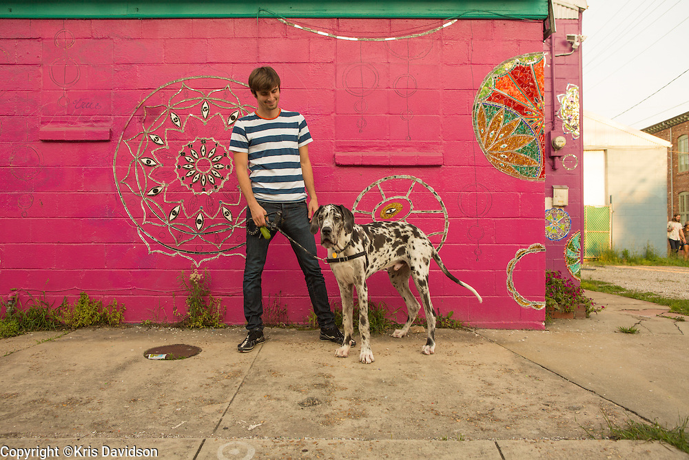 New Orleans resident Kirill Kourtchikov, recently relocated from New York City, with his Great Dane, Loki, out for a walk in the Bywater. The pink wall art is a work-in-progress by mosaic artist Laurel True.