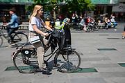 In Eindhoven fietst een meisje met haar jas over het stuur over het 18 septemberplein.<br /> <br /> In Eindhoven a young woman cycles at the city center.
