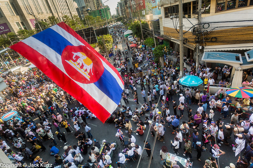 "13 JANUARY 2014 - BANGKOK, THAILAND: Anti-government protestors in the Asok intersection in Bangkok. Tens of thousands of Thai anti-government protestors took to the streets of Bangkok Monday to shut down the Thai capitol. The protest was called ""Shutdown Bangkok"" and is expected to last at least a week. The Shutdown Bangkok protest is a continuation of protests that started in early November. There have been shootings almost every night at different protests sites around Bangkok, including two Sunday night, but the protests Monday were peaceful. The malls in Bangkok stayed open Monday but many other businesses closed for the day and mass transit was swamped with both protestors and people who had to use mass transit because the roads were blocked.    PHOTO BY JACK KURTZ"