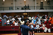 Hip Hop legend, Kurtis Blow, 47, is singing while Christian devotees are dancing at his beat, during a Mass Service at the Hip Hop Church in Harlem, New York, NY., on Thursday, July 21, 2006. A new growing phenomenon in the United States, and in particular in its most multiethnic city, New York, the Hip Hop Church is the meeting point between Hip Hop and Christianity, a place where ëGodí is worshipped not according to religious dogmatisms and rules, but where the ëHoly Spirití is celebrated by the community through young, unique, passionate Hip Hop lyrics. Its mission is to present the Christian Gospel in a setting that appeals to both, those individuals who are confessed Christians, as well as those who are not regularly attending traditional Services, while helping many youngsters from underprivileged neighbourhoods to feel part of a community, to make them feel loved and to help them not to give up when problems arise. The Hip Hop Church is not only forward-thinking but it also has an important impact where life at times can be difficult and deceiving, and where young people can be easily influenced for the worst purposes. At the Hip Hop Church, members are encouraged to sing, dance and express themselves in any way that the ëSpirit of Godí moves them. Honours to students who have overcome adversity, community leaders, church leaders and some of the unsung pioneers of Hip Hop are common at this Church. Here, Hip Hop is the culture, while Jesus is the centre. Services are being mainly in Harlem, where many African Americans live; although the Hip Hop Church is not exclusive and people from any ethnic group are happily accepted and involved with as much enthusiasm. Rev. Ferguson, one of its pioneer founders, has developed ëHip-Hop Homileticsí, a preaching and worship technique designed to reach the children in their language and highlight their sensibilities, while bringing forth Christianity. This ëKeep It Realí evangelism style is the centrepiece of Rev. Ferguson