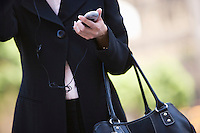 Businesswoman with handbag and  mobile, mid section