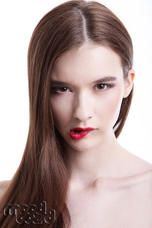 Portrait of beautiful young woman biting her lip against white background