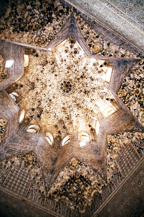 Interior of the dome of the Hall of Ambassadors, Alhambra.  Windows along the top of the dome shed light on the elaborate stalagtite ornament.