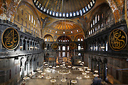 High angle view of interior and domes showing Islamic elements in the ceiling and the mirhab below, Hagia Sophia, 532-37, by Isidore of Miletus and Anthemius of Tralles, Istanbul, Turkey. Hagia Sophia, The Church of the Holy Wisdom, has been a  Byzantine church and an Ottoman mosque and is now a museum. The current building, the third on the site, commissioned by Emperor Justinian I, is a very fine example of Byzantine architecture. The historical areas of the city were declared a UNESCO World Heritage Site in 1985. Picture by Manuel Cohen.