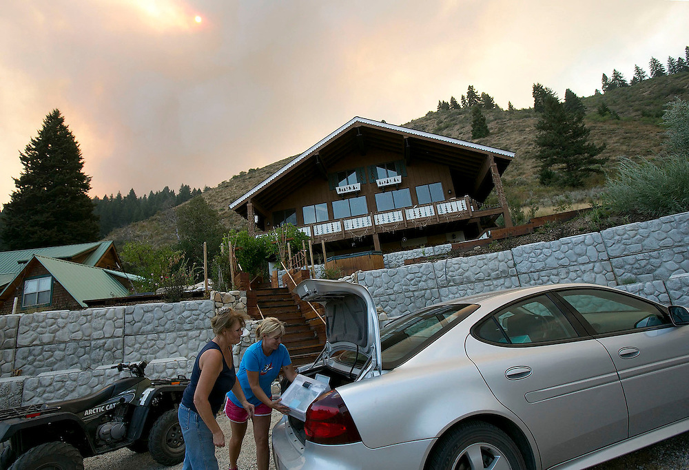 Diana Whitted (left) and an unidentified friend remove cherished belongings from a friends house near Pine, Idaho while the Elk fire burns in the background. Sunday August 11, 2013