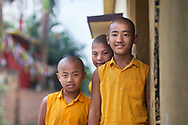 Young Tibetan expatriates stand outside the door of their Buddhist study hall in the Sera Monastery in Bylakuppe, Karnataka, India.