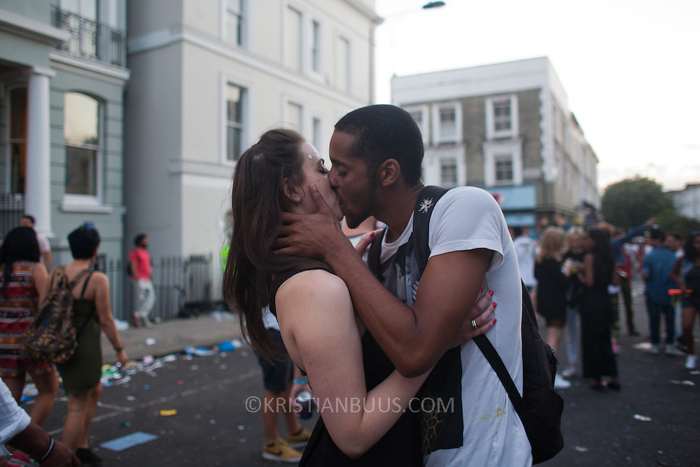 Lovers snogging in the street. The streets are emptying quickly as the sun sets and the parades are over.  The Notting Hill Carnival has been running since 1966 and is every year attended by up to a million people. The carnival is a mix of amazing dance parades and street parties with a distinct Caribbean feel.