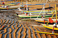The beach at Sanur at low tide. Boats are beached an the ripples of the tide are etched into the drying sand.