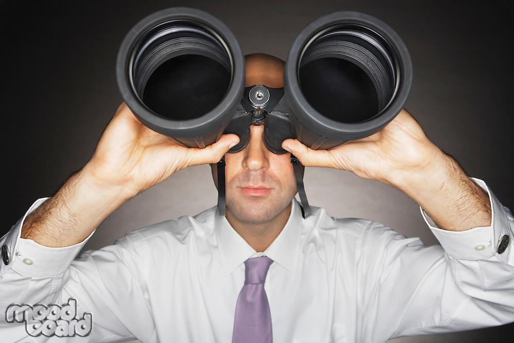 Balding Middle-aged businessman looking through large binoculars