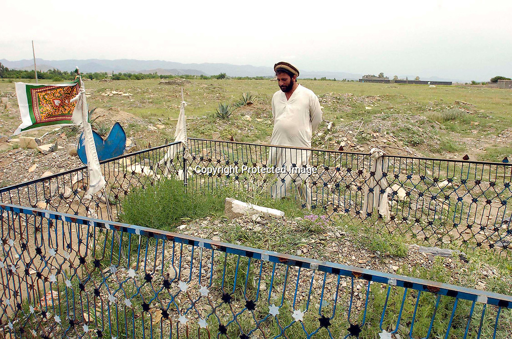 Shahpoor talks about his brother Diliwar at his grave in the the town of Yakubi in the district of Khost, Afghanistan May 2, 2005. Diliwar, a 22-year-old farmer and part-time taxi driver, died in December 2002 while being held in the main United States air base at Bagram, north of Kabul. His death was ruled a homicide by the Army medical examiner.<br />