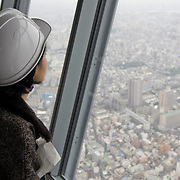 A member of the media takes in the view of Tokyo 350m above ground from the first observatory of the nearly completed Tokyo Sky Tree tower in Tokyo, Japan, Saturday, October 30, 2011. Tokyo Sky Tree, the tallest self-supporting tower and second tallest building in the world, is scheduled to be opened to the public in May, 2012. (Albert Siegel)