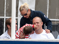 GATCOMBE, ENGLAND- AUG 7: Zara and Mike Tindall with Peter and Autumn Phillips watch a display in the main arena at the British Festival of Eventing at Gatcombe Park in Gloucestershire. <br /> The child of James Simpson Daniel (Gloucester Rugby and Usher at wedding) plays with Mike.