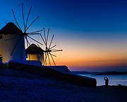 Twilight Windmills of Mykonos - As sentinels now purely for iconic images, the windmills of Mykonos pose for their tourist moment and his iPhone.<br /> <br /> I waited until he positioned himself just where I suspected he would, and then captured the image just as he did so quickly before moving on.<br /> <br /> f 9 @ 2 s, 200 ISO<br /> 24.0-70.0 mm f/2.8 at 50 mm on NIKON D850