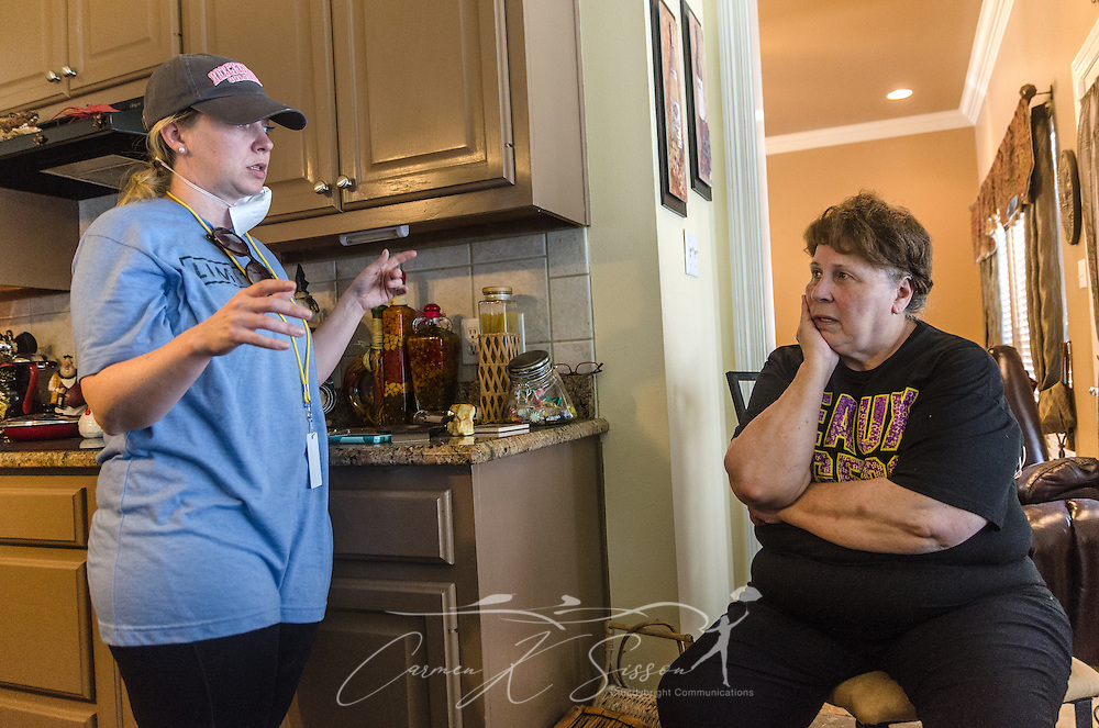 Sarah Farley, associate director of Louisiana State University's Baptist Collegiate Ministry, discusses mold removal with homeowner Paulette LaCombe, Sept. 3, 2016, at a flood-damaged home in Denham Springs, La. Farley helped organize a massive mud out event, bringing more than 450 student members of LSU Baptist Collegiate Ministry and other collegiate church ministries from six states, to help survivors of the mid-August flood.  (Photo by Carmen K. Sisson)