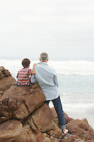 Father and son (5-6) sitting on rock facing ocean back view
