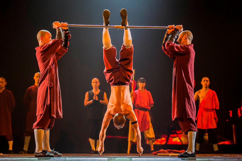 "A monk does a headstand on his finger tips - Twenty Shaolin monks, from their  temple in the foothills of the Song Shang mountain range in China's Henan province, take to the stage to demonstrate their martial arts expertise in an 'awe-inspiring' performance. SHAOLIN is a display of theatre and physical prowess in which the cast perform ""superhuman"" feats. The show combines traditional Shaolin Kung Fu, inch perfect choreography with dramatic lighting and sound that evokes the spirit of their tradition – their Temple being the birthplace of Kung Fu.  These are the very best Shaolin Kung Fu experts on the planet and they have come together to create this show. The Shaolin Monks are lifted aloft on sharpened spears, break marble slabs with their heads, perform handstands on two finger tips,splinter wooden staves with their bodies, break bricks on their heads and fly through the air in a series of incredible back flips. The show embarks upon a three-week run at The Peacock Theatre, London from 29 September – 17 October 2015."