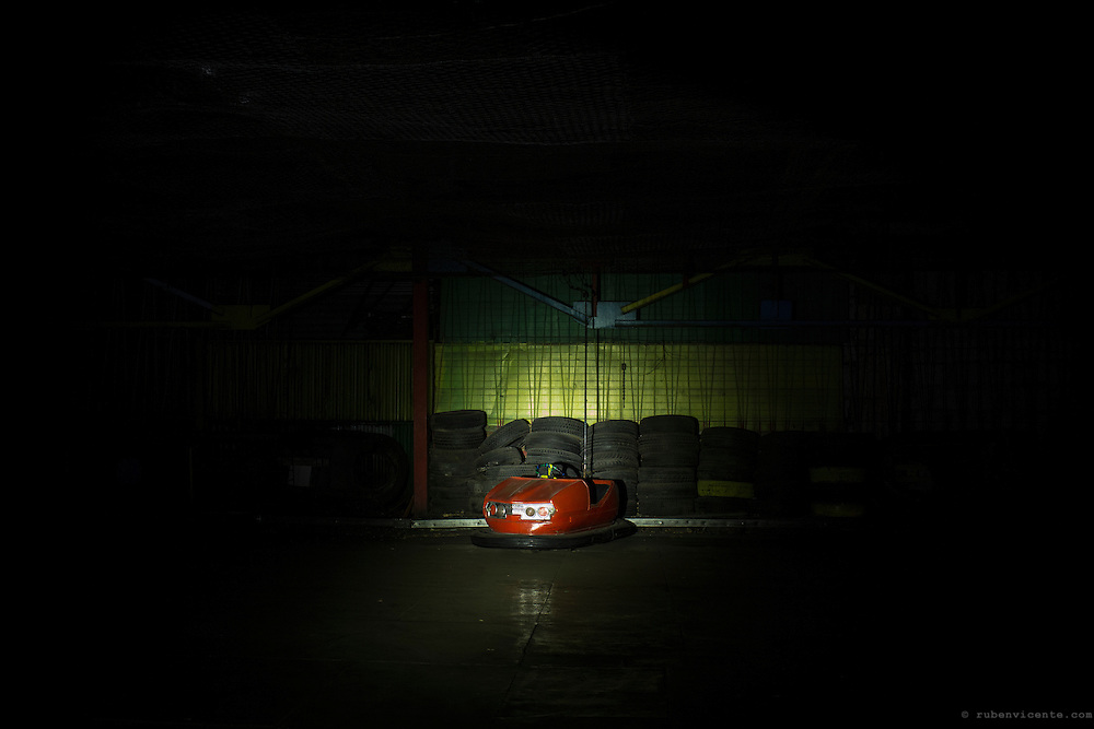Abandoned red bumper car in Gyumri park at night. Armenia
